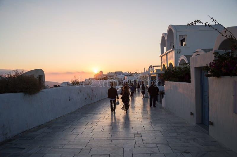 Ludzie Chodzi w kierunku zmierzchu z Dennym widokiem w Oia, Santorini, obraz royalty free