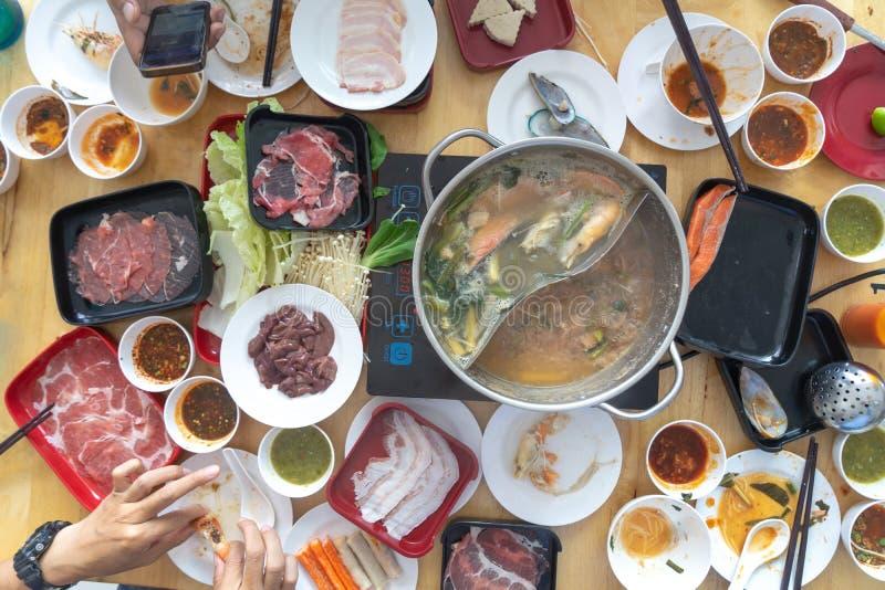 Ludzie cieszą się jedzący Shabu Sukiyaki, Japoński jedzenie odgórny widok wpólnie obraz stock