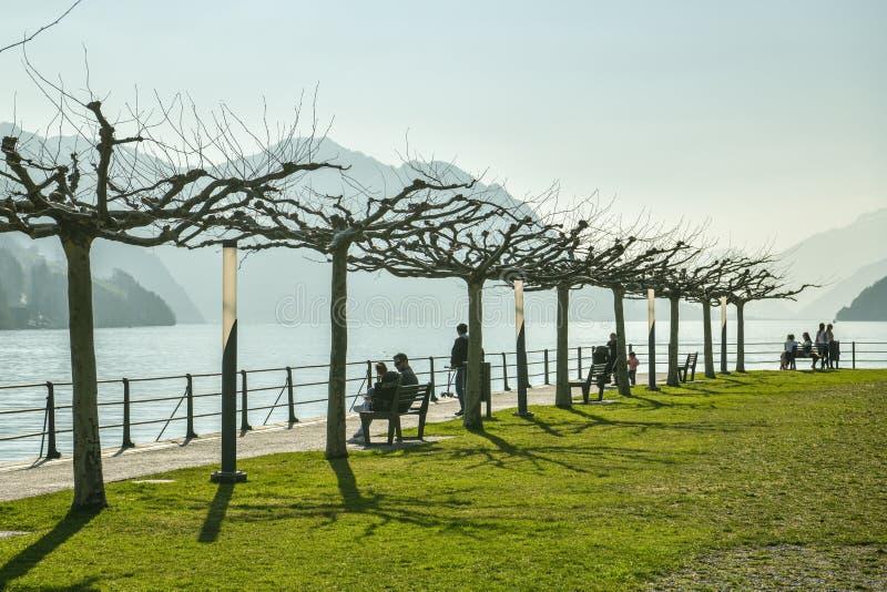 Ludzie cieszy się ciepłego dzień w małym parku w Brunnen, Szwajcaria fotografia stock