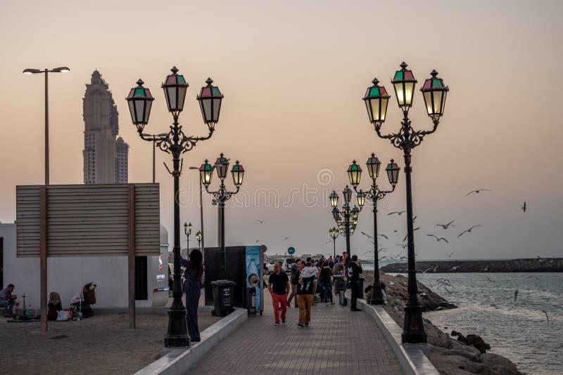 Ludzie cieszy się przy Cornich Marina zaświecali z Lampost przy wieczór, Abu Dhabi, UAE zdjęcie stock