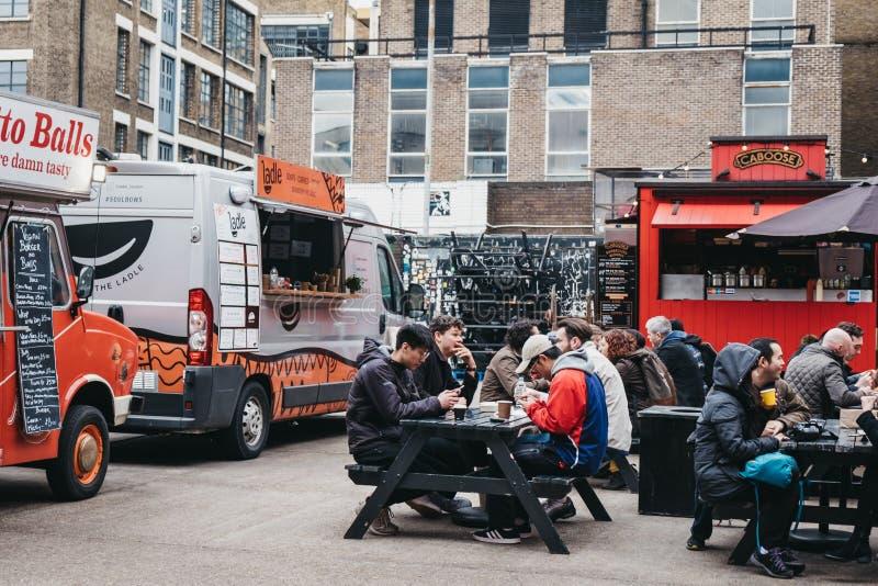 Ludzie cieszy się ulicznego jedzenie w Ely jardzie, Ceglany pas ruchu, Wschodni Londyn, UK zdjęcie royalty free