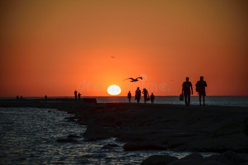 ludzie cieszy się zmierzch na brakewater w morzu zdjęcia royalty free