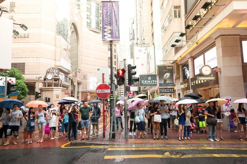 Ludzie czeka krzyżować przez ruchliwych ulic przy Hong Kong czasami zdjęcie stock