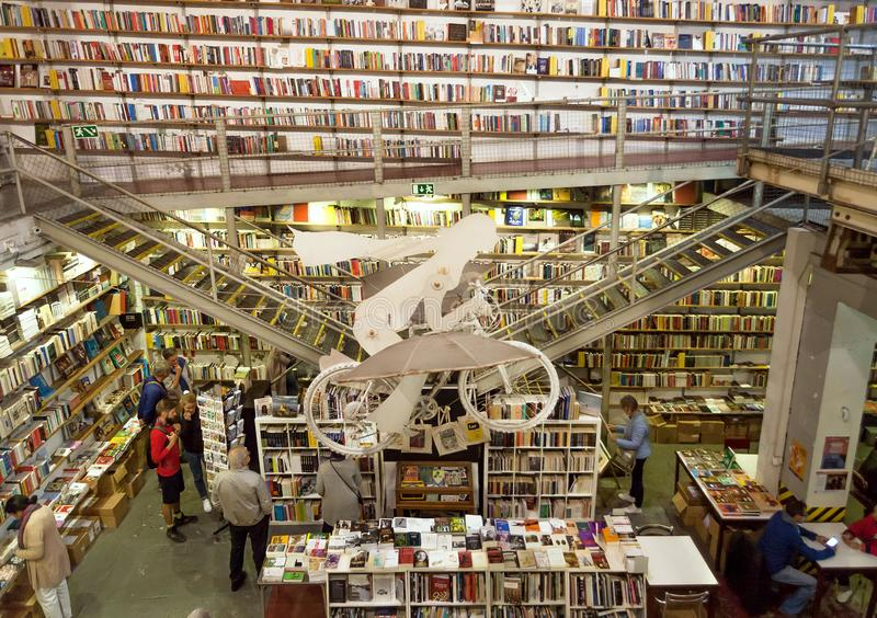 Ludzie czyta nowe książki wśrodku popularnego bookstore Ler Devagar z grafika i wiele półkami na książki zdjęcia royalty free