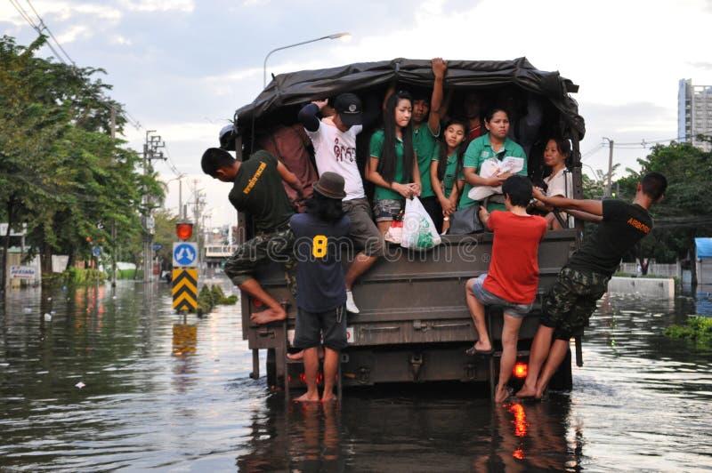 Ludzie dojeżdżać do pracy w wojsko ciężarówce w zalewającej ulicie w Bangkok, Tajlandia, w Październiku 2011 obrazy stock