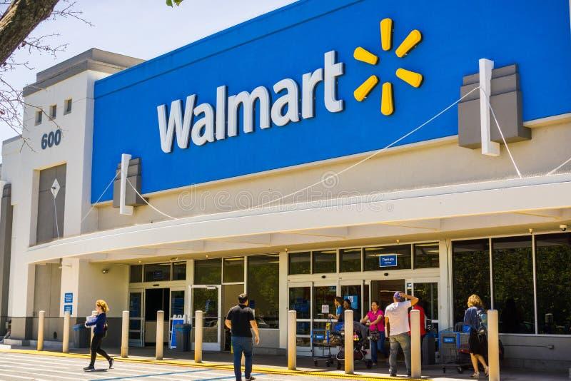 Ludzie iść wewnątrz i przychodzi z Walmart sklepu obrazy stock