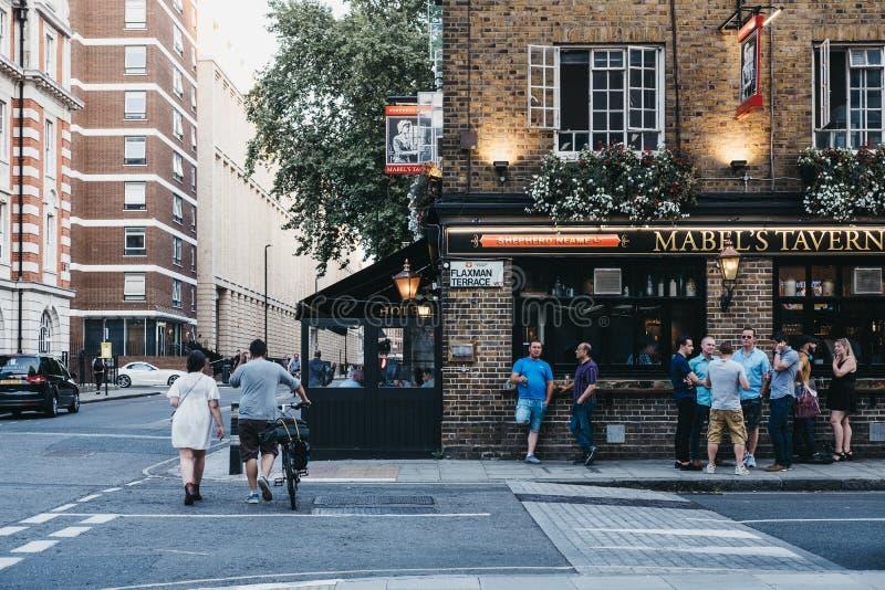 Ludzie i samochody przed Mabel tawerny pubem, królewiątko krzyż, Lo obraz royalty free