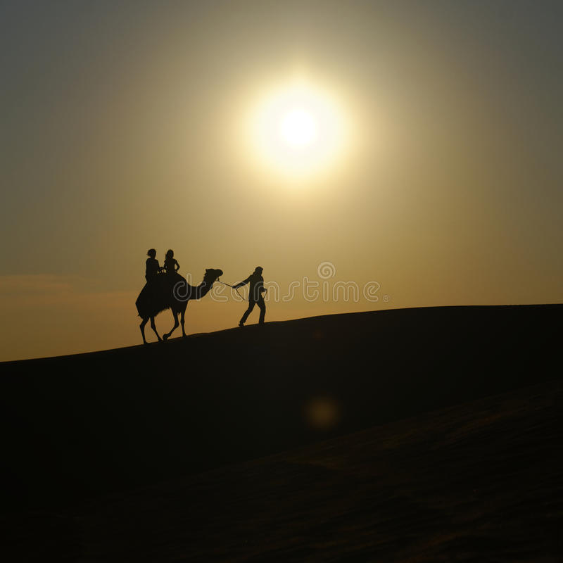 Ludzie i wielbłąd na pustyni zdjęcia royalty free