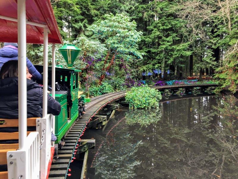 Ludzie jadący pociągiem świątecznym w wigilię w pięknych lasach Stanley Park, Vancouver, Kanada zdjęcie stock