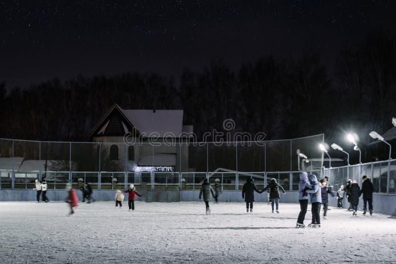 Ludzie jeździć na łyżwach na zimy łyżwiarskim lodowisku obraz stock