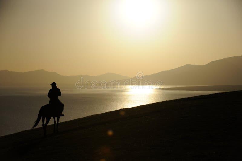 ludzie jeździeckiego konia przy wschodem słońca fotografia royalty free