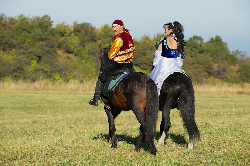 Ludzie jest ubranym krajowe suknie jadą na horseback przy wsią, Almaty, Kazachstan zdjęcie stock