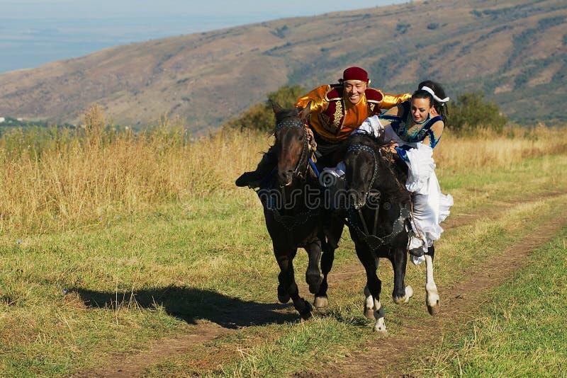Ludzie jest ubranym krajowe suknie jadą na horseback przy wsią, Almaty, Kazachstan obraz royalty free
