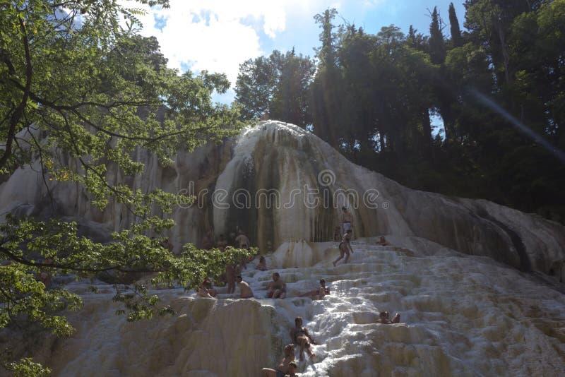 Ludzie kąpać się w Bagni San Filippo naturalnych termicznych basenach obraz stock