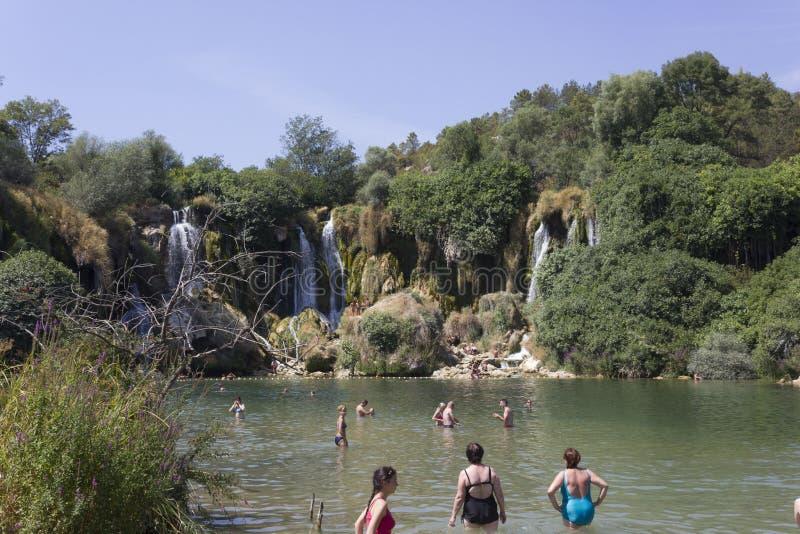 Ludzie kąpać się w naturalnym parku Kravice siklawy zdjęcie stock