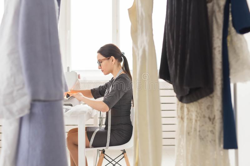Ludzie, krawczyna i mody pojęcie, - Zamyka w górę portreta pracującego miejsca projektant mody z szwalną maszyną zdjęcia royalty free