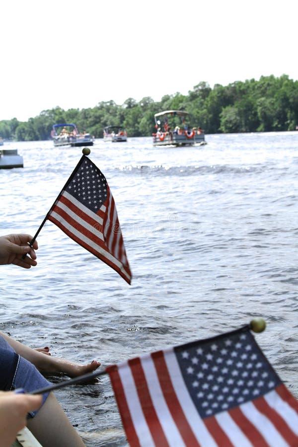 Ludzie macha flaga amerykańskie przy przelotną pontonową paradą gdy siedzą na krawędzi dok zdjęcia royalty free
