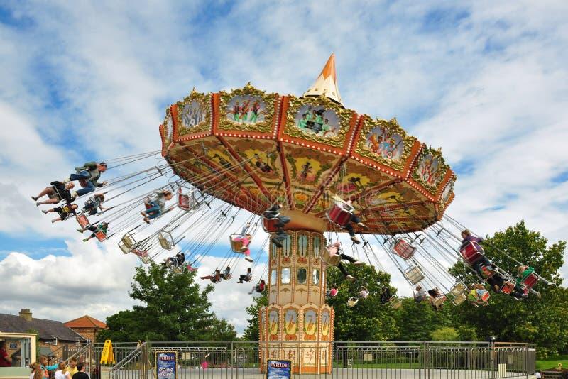 Ludzie na carousel pod niebieskim niebem z chmurami