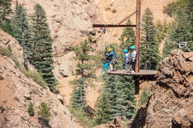 Ludzie na platformie w górach dostaje gotowy rappel puszek - obsługuje pomaga kobiety w nicielnicie gdy dostaje gotową iść podcza obraz royalty free