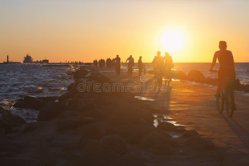Ludzie na rowerach jadą wzdłuż dajka w morzu przy zmierzchem obrazy royalty free