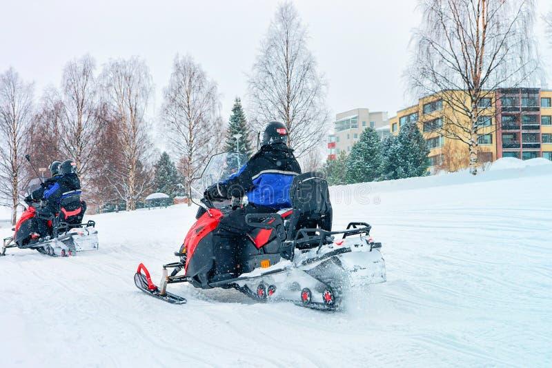 Ludzie na Snowmobiles przy zimą Finlandia Lapland w bożych narodzeniach zdjęcia stock