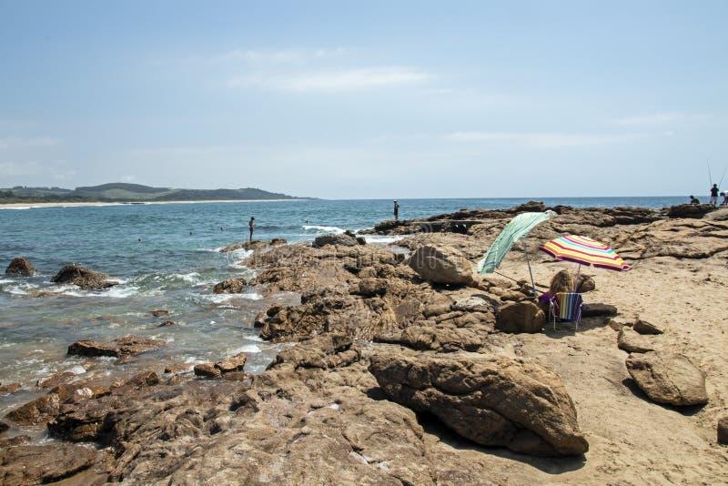 Ludzie na wczesny poranek plaży skałach przy Scottburgh fotografia stock