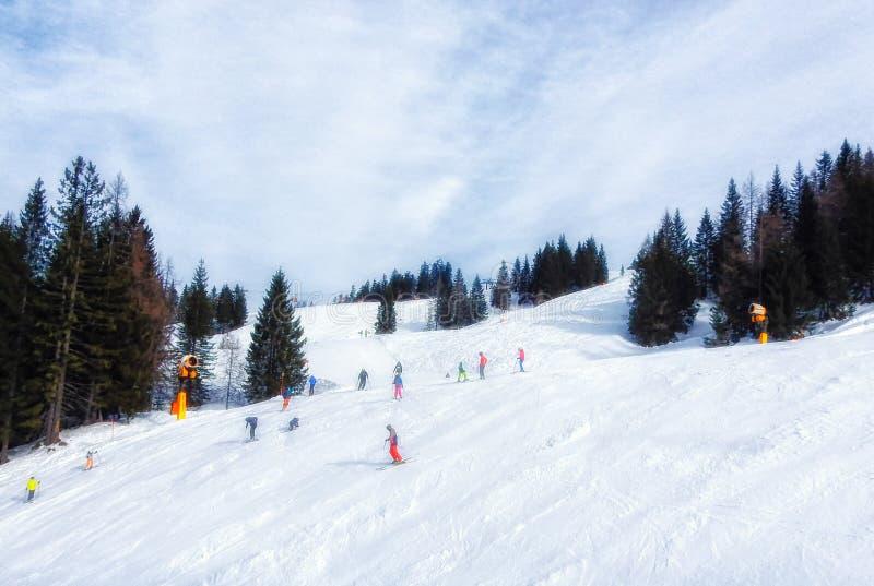 Ludzie narciarstwa i jazda na snowboardzie na skłonie przy ośrodkiem narciarskim zdjęcie royalty free