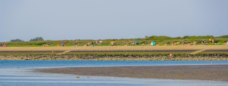 Ludzie odtwarzać nagi przy nudystyczną plażą Tholen, Bergse diepsluis, Oosterschelde holandie zdjęcie stock