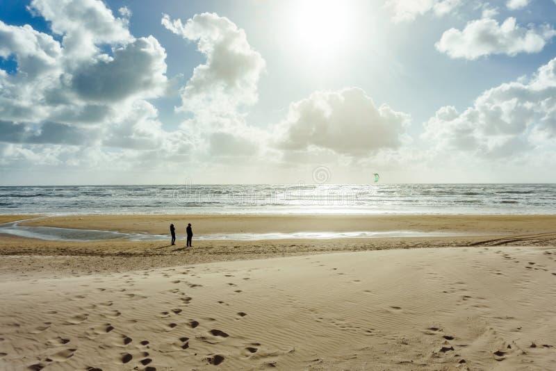 Ludzie ogląda kitesurfer przy panoramicznym widokiem borowinowego mieszkania morze obraz stock