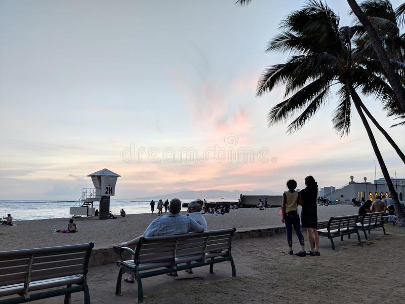 Ludzie oglądają dramatycznego półmrok nad oceanem na Kaimana plaży fotografia stock