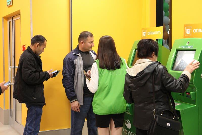 Ludzie otrzymywają poradę ekspertą na bankowość usługach blisko ATM Sb obraz stock