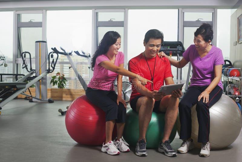 Ludzie patrzeje cyfrową pastylkę w gym zdjęcie royalty free