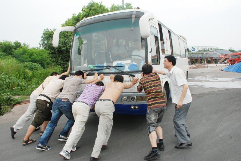 Ludzie pchają autobus. obrazy royalty free