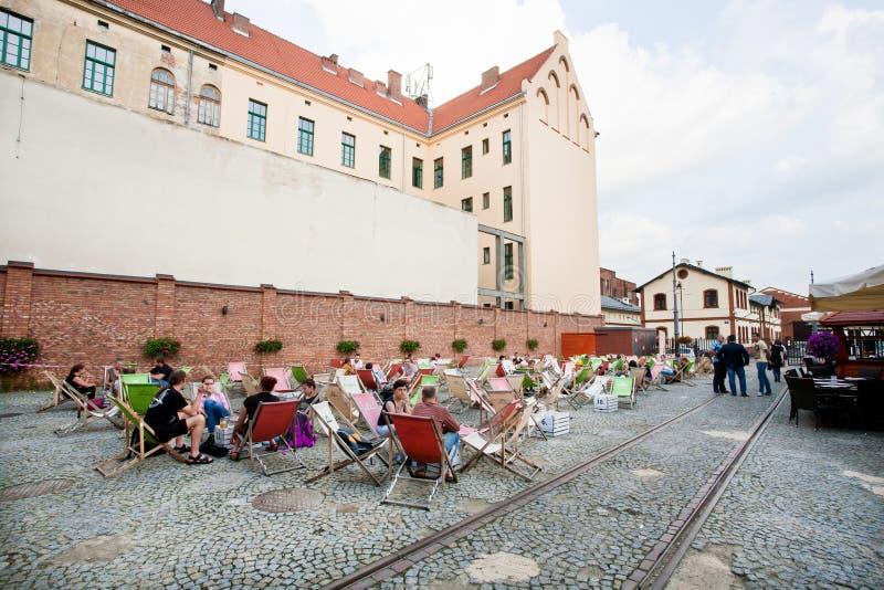 Ludzie pije i siedzi w sunbeds uliczna kawiarnia w starej tramwajowej zajezdni obrazy royalty free