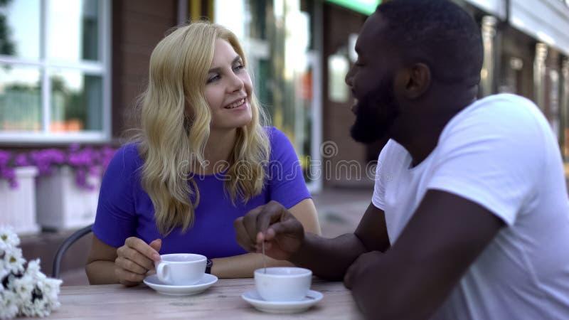 Ludzie pije kawę w plenerowej kawiarni, romantyczna data szczęśliwa mieszana biegowa para fotografia royalty free