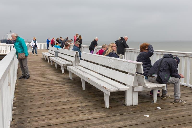 Ludzie przy drewnianym mola Cuxhaven czekaniem dla promu Helgoland zdjęcie stock