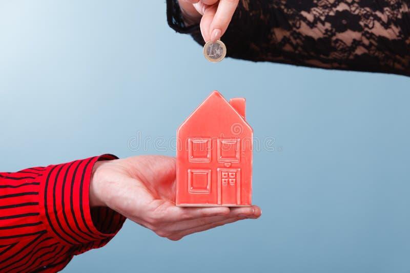Ludzie ręk z małym domem i srebną monetą obraz stock