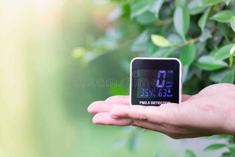 Ludzie ręki trzyma PM 2 5 detektor sprawdza pył na zamazanym zielonym liściu obrazy stock