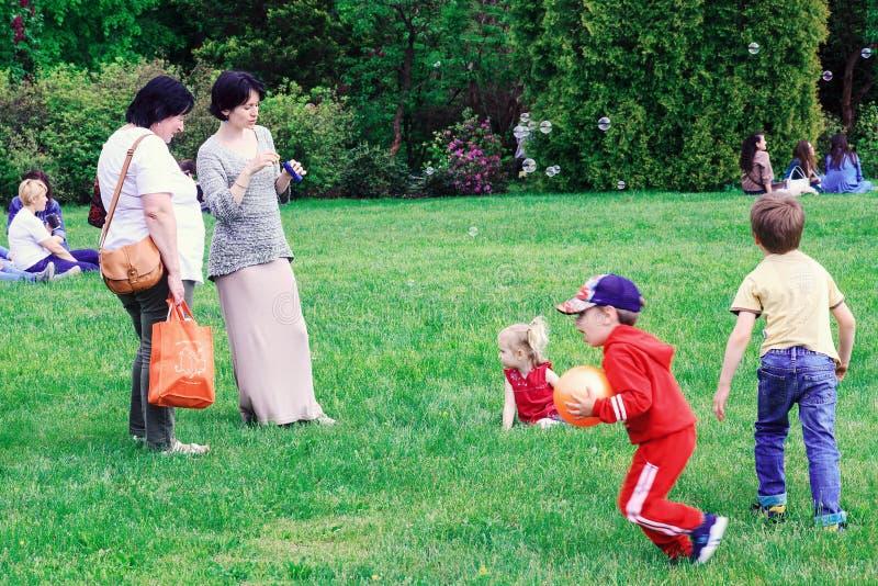 Ludzie relaksują w lato parku Dzieciaki plaing z mydlanymi bąblami zdjęcie stock