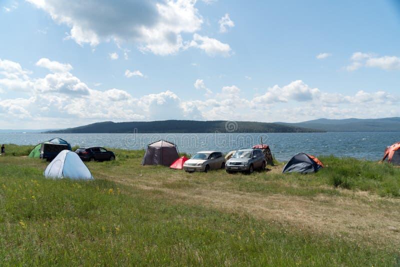Ludzie relaksują w namiotu obozie na brzeg Wielki jezioro w lecie zdjęcia royalty free