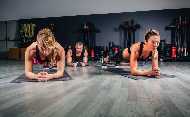 Ludzie robić pchają podnoszą w sprawności fizycznej klasie obraz royalty free
