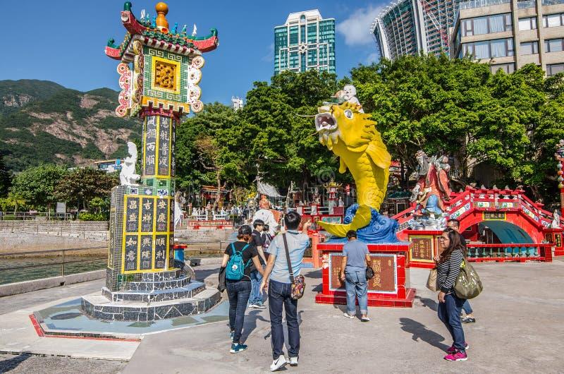 Ludzie rzucają monetę przy usta duża kolor żółty ryba wierzy szczęsliwą Kuan yin świątynię zdjęcia stock