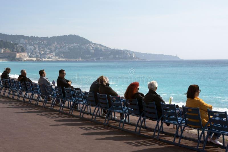 Ludzie siedzą na sławnych błękitnych krzesłach na Promenade Des Anglais, oglądają lazurowego morze i cieszą się ciepłego światło  zdjęcie stock