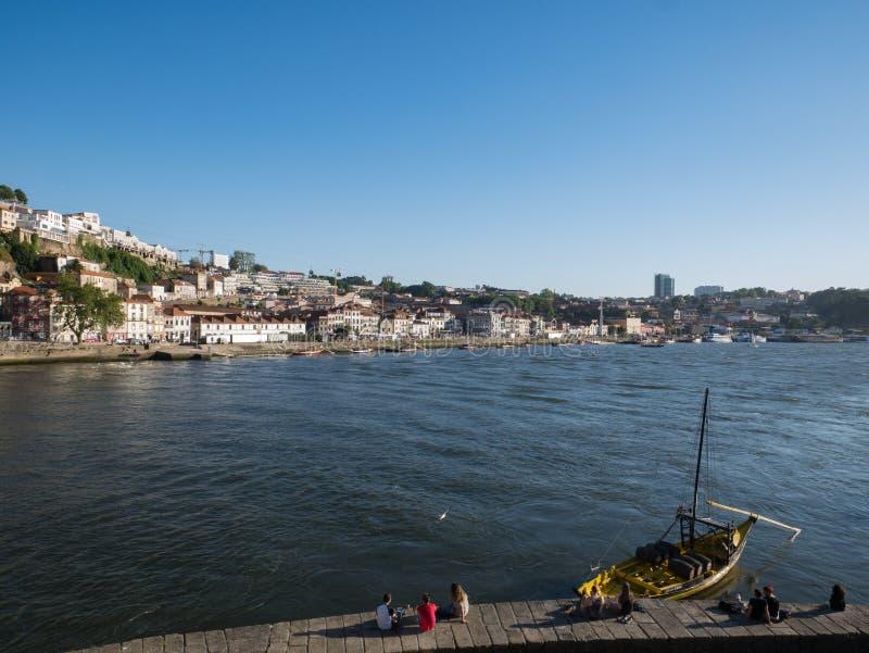 Ludzie siedzą na nabrzeżu na Douro rzece, Porto, Portugalia zdjęcia stock