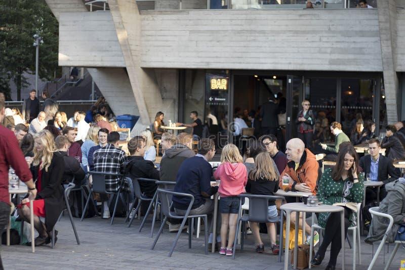 Ludzie siedzą w ulicznej kawiarni blisko Krajowego teatru na Thames rzeki bulwarze zdjęcia royalty free