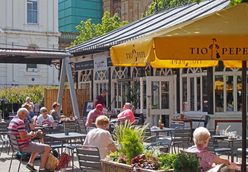 Ludzie siedzący przed kawiarnią lekarską w południowym porcie w jasnym letnim słońcu obraz royalty free