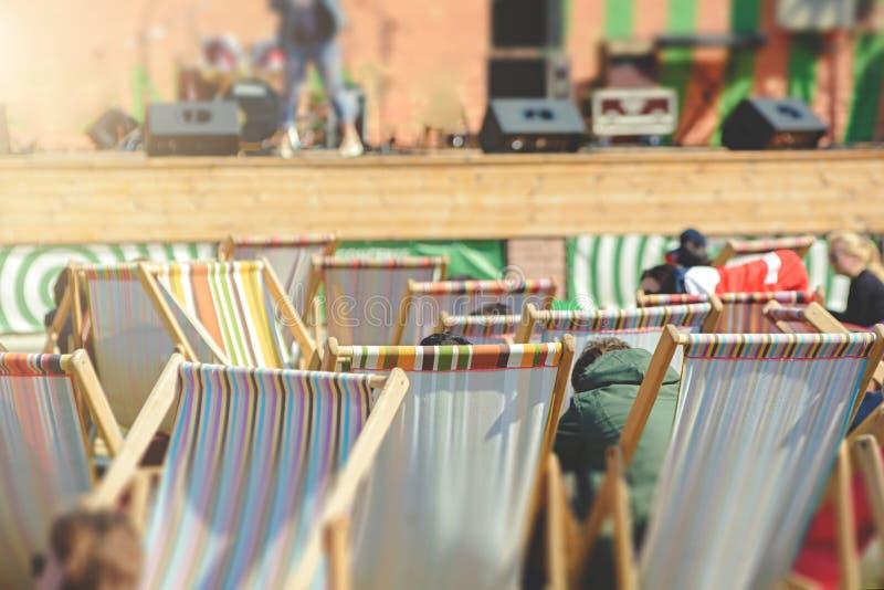 Ludzie siedzący w fotelach spoczywają na koncercie ulicznym obrazy stock