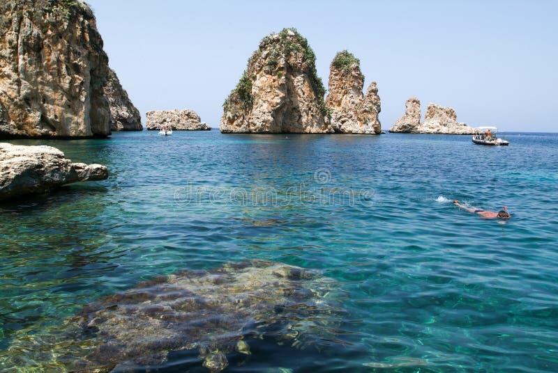 Ludzie snorkeling przed Faraglioni przy Scopello na Sicily fotografia stock