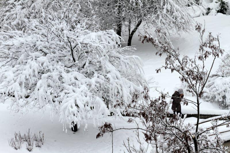 Ludzie spaceru na bardzo śnieżnym chodniczku Ludzie kroczą na bezpański drodze przemian Lodowaty chodniczek Lód na chodniczkach obrazy royalty free