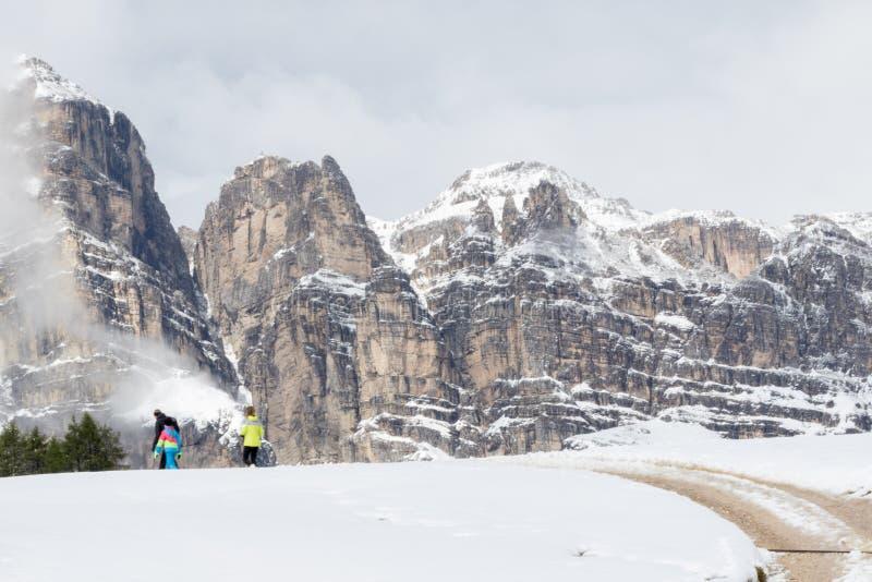 ludzie spacerują w wysokogórskiej scenerii z śnieżystymi łąkami wzdłuż drogi obrazy royalty free